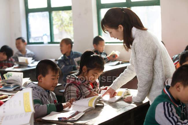 Китайская сельская учительница и школьницы в классе — стоковое фото