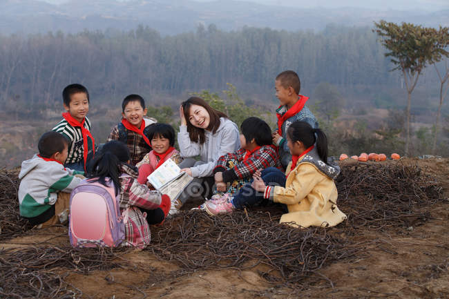 Young female rural teacher reading book to pupils in outdoor learning — стокове фото