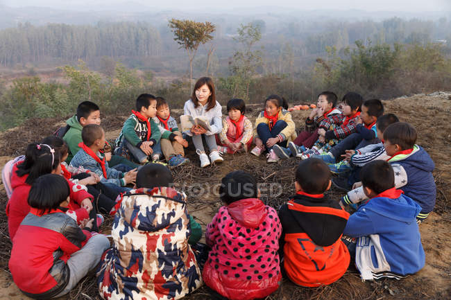 Young female rural teacher reading book to pupils in outdoor learning — Stock Photo