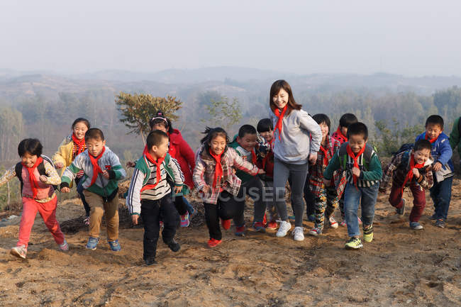 Young female teacher and happy chinese school students playing outdoor — Stock Photo