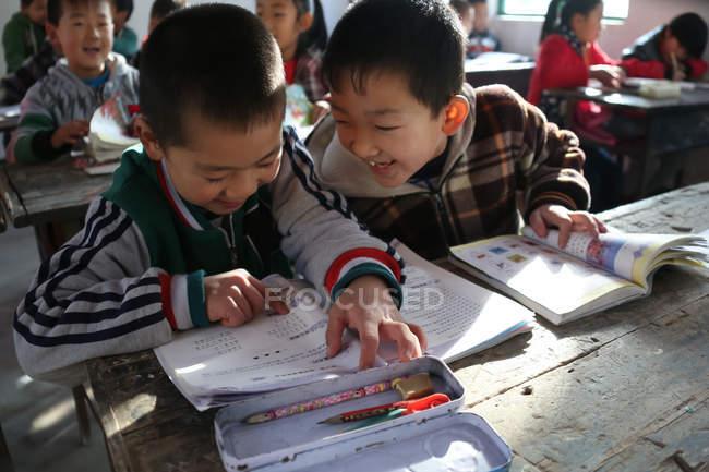 Asiatique écoliers étudiant dans rural primaire école — Photo de stock