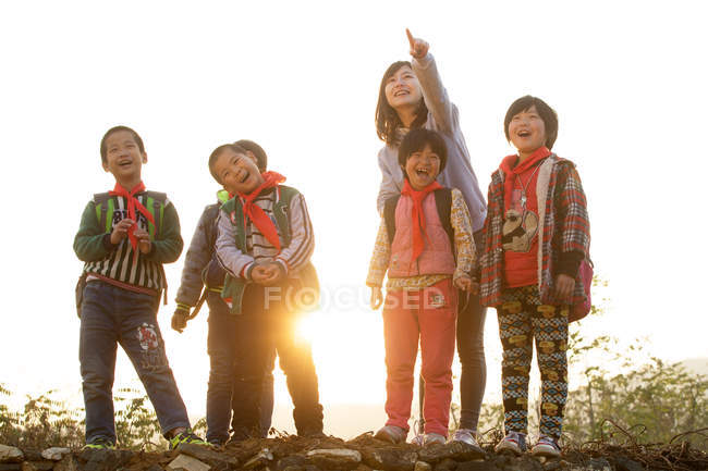 Rural female teacher pointing with finger for chinese students standing outdoor — Stock Photo