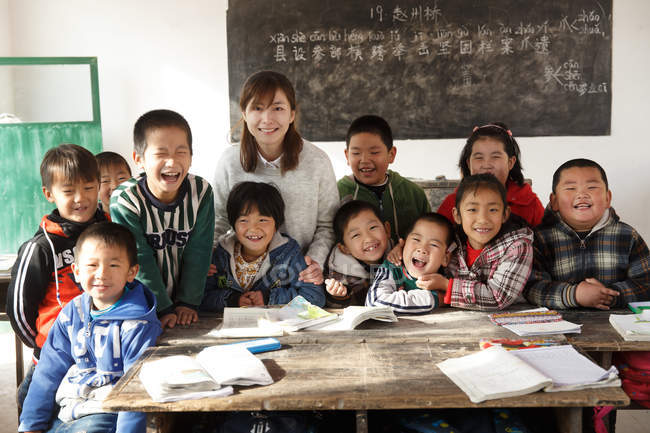 Chinese rural female teacher and pupils smiling at camera in the classroom — Stock Photo