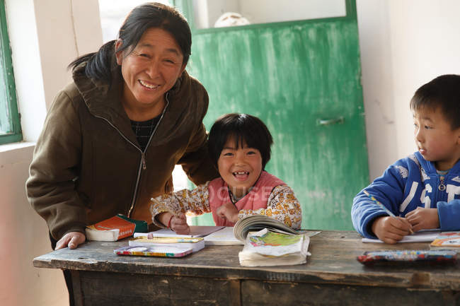 Rural female teacher and chinese pupils studying in the classroom — стокове фото