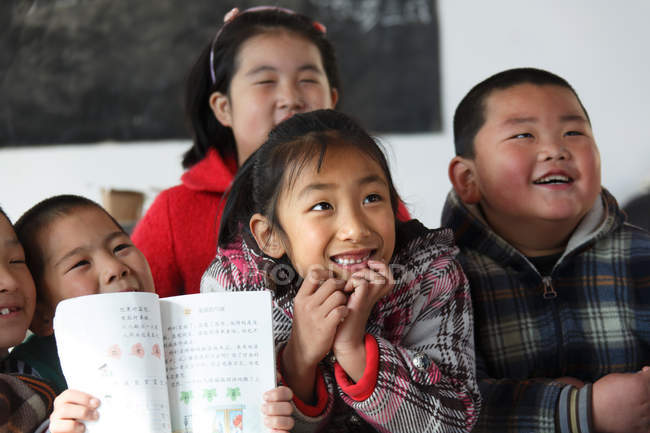 Cheerful asian school students studying in rural primary school — Stock Photo