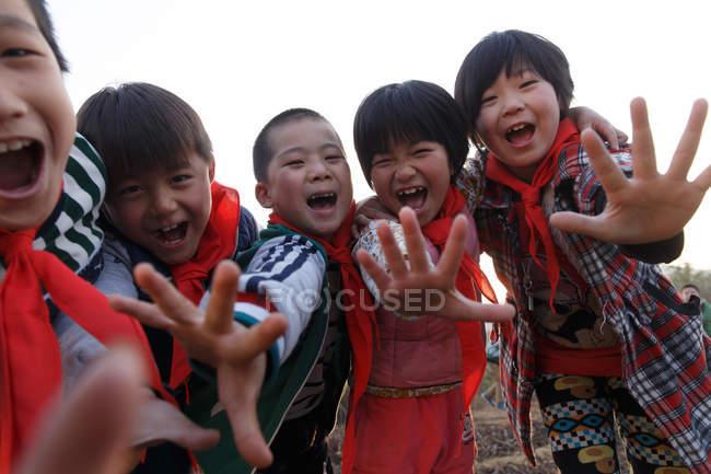 Счастливые сельские китайские школьники смеются над камерой на улице — стоковое фото