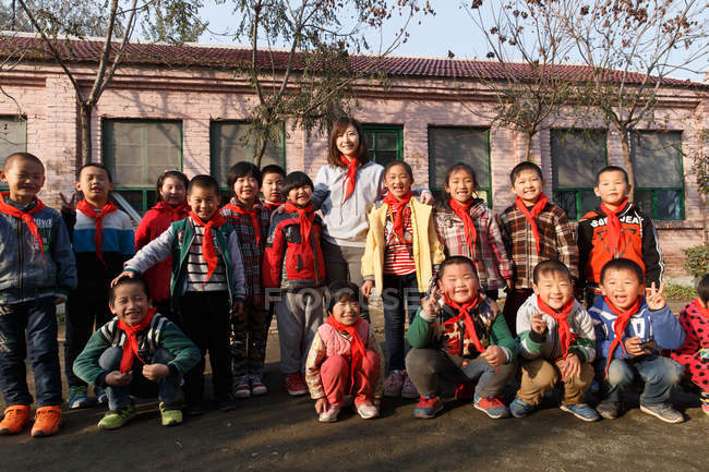 Rural female teacher and happy chinese pupils standing together in school yard — Stock Photo