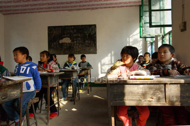 Focused Chinese school students sitting at desks and studying in rural primary school — стокове фото