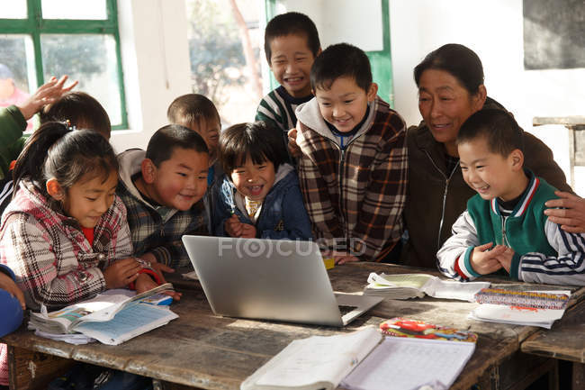 Rural female teacher and pupils using laptop computer together in school — стокове фото