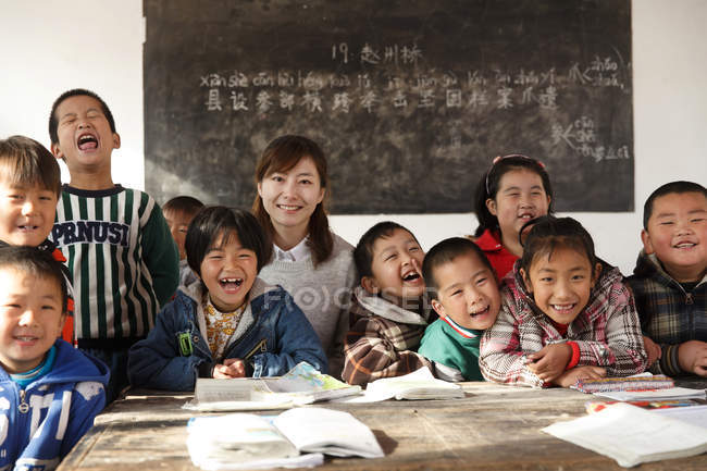 Rural female teacher and chinese pupils laughing in the classroom — Stock Photo
