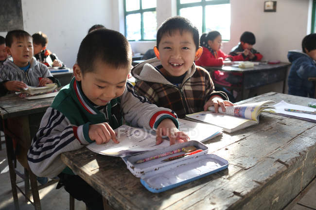 Chinese school students expressing positivity while studying with textbooks in rural primary school — стокове фото