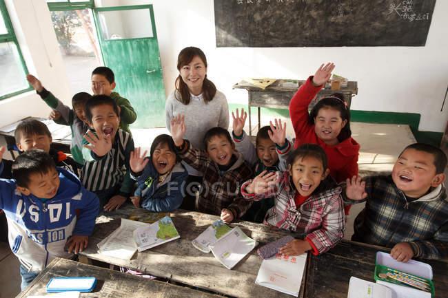 Visão de alto ângulo da professora rural e alunos chineses levantando as mãos e sorrindo para a câmera em sala de aula — Fotografia de Stock