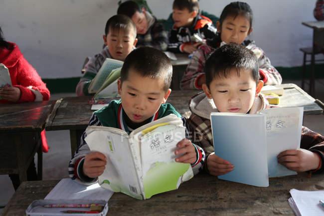Китайские школьники учатся с книгами в сельской начальной школе — стоковое фото