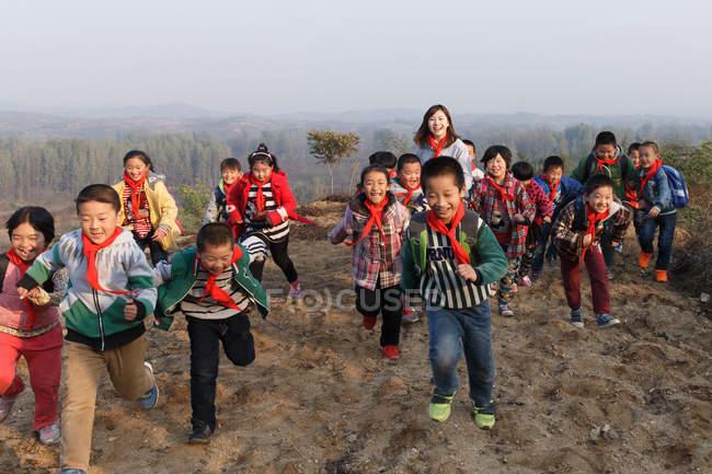 Молодые женщины-учителя и китайские школьники играют в сельской местности — стоковое фото