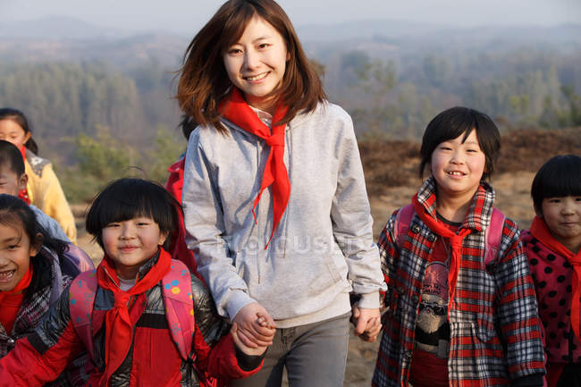Young female teacher walking outdoor with rural chinese students — стокове фото