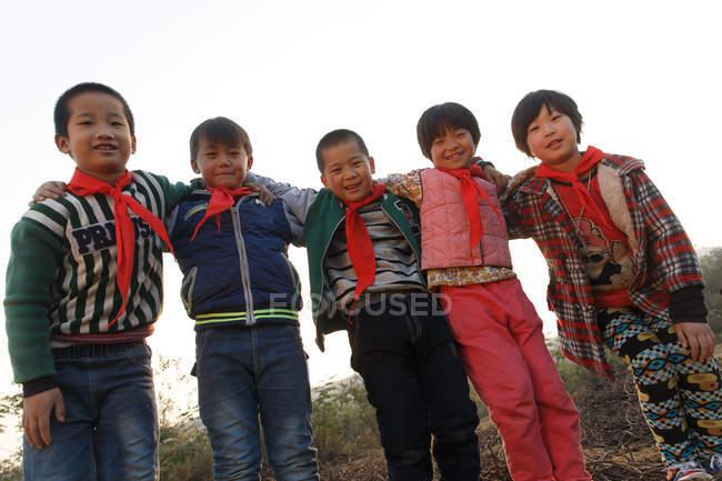 Низкий угол зрения счастливых китайских учеников, стоящих вместе и улыбающихся в камеру на открытом воздухе — стоковое фото