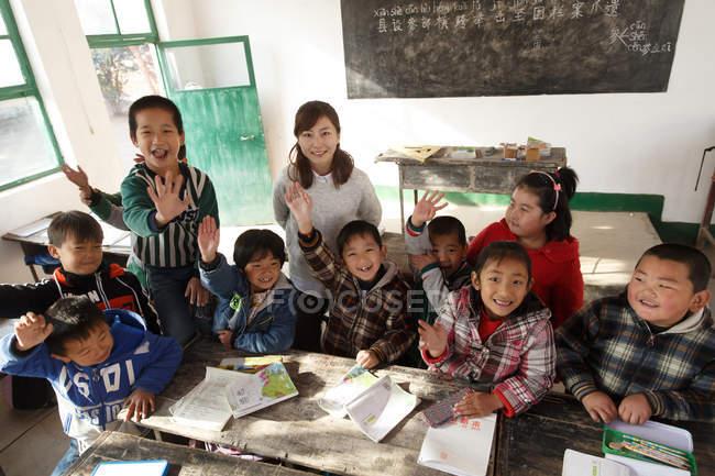 Visão de alto ângulo da professora rural e alunos chineses sorrindo para a câmera em sala de aula — Fotografia de Stock