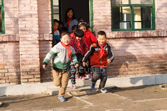 Rural chinese teacher and pupils in school and on yard — Stock Photo