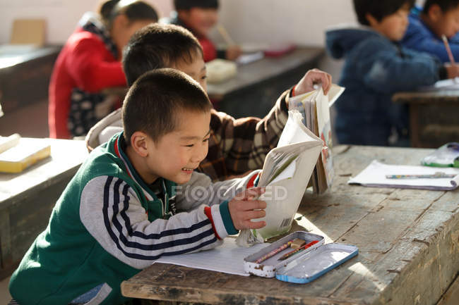 Chinese school students studying with textbooks in rural primary school — Stock Photo