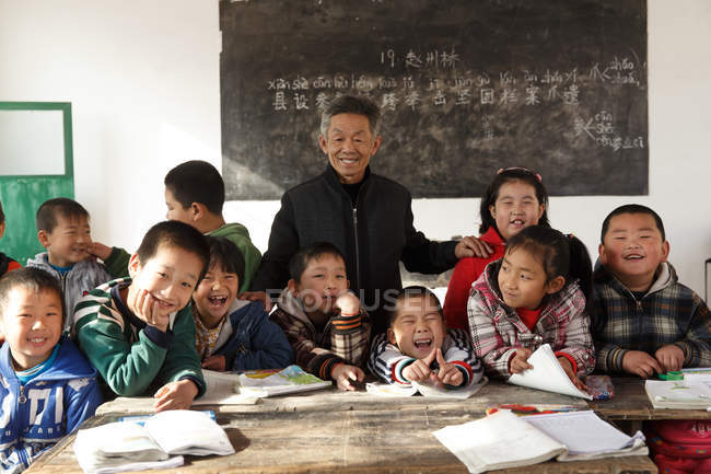 Male teacher and chinese pupils smiling at camera in classroom — стокове фото
