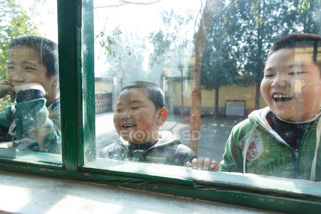 Élèves d'école primaire regardant par la fenêtre à l'intérieur du bâtiment d'école primaire — Photo de stock