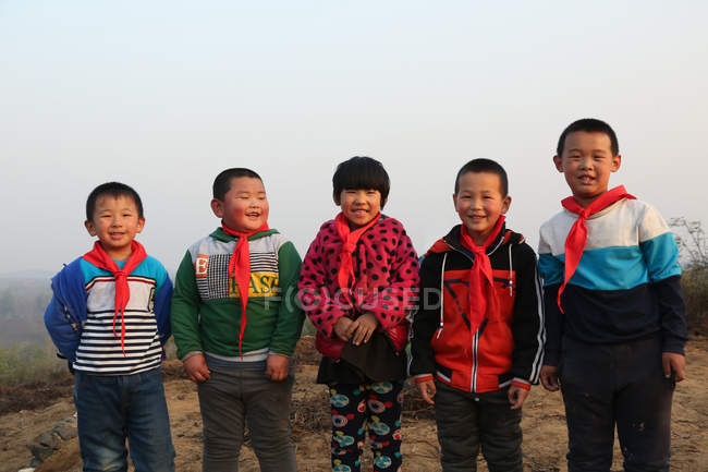 Happy chinese pupils standing together and smiling at camera outdoor — Stock Photo
