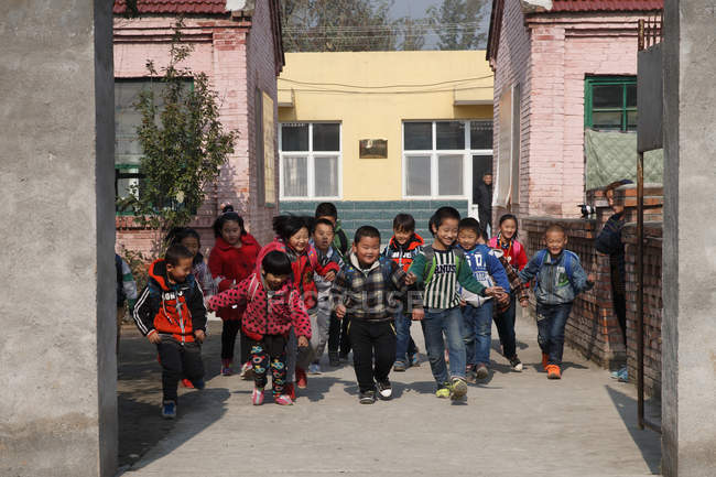 Happy chinese rural pupils coming home from school — Stock Photo