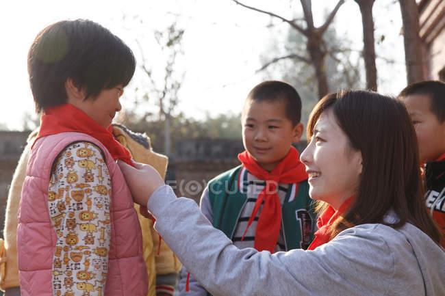 Chinesische Lehrerin und Schüler in roten Tüchern auf dem Schulhof — Stockfoto