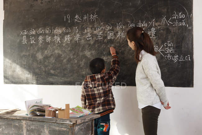 Young female chinese teacher looking at elementary school student writing on chalkboard — Stock Photo