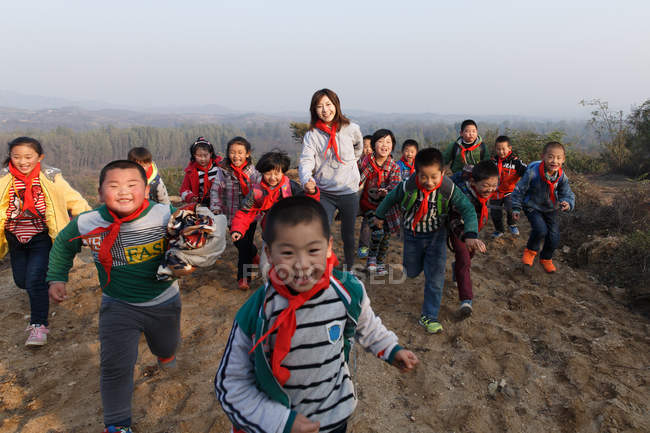Young female teacher and rural chinese school students playing outdoor — Stock Photo