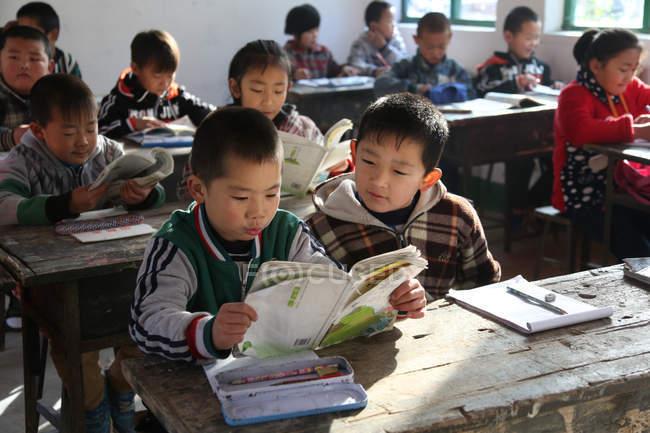 Китайские школьники учатся с учебниками в сельской начальной школе — стоковое фото