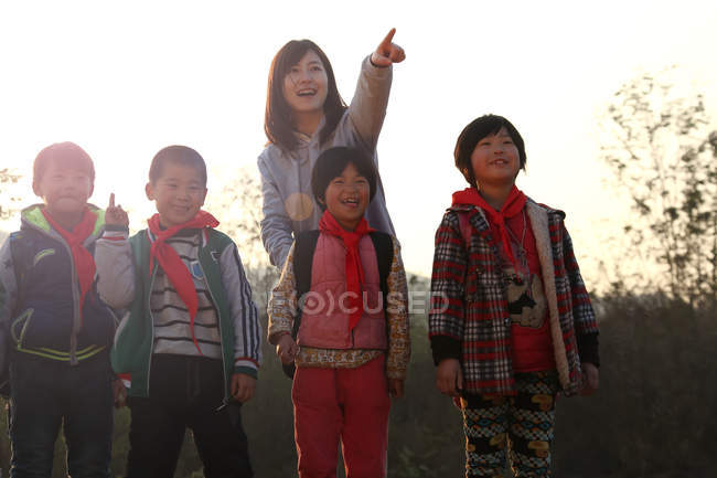 Rural female teacher pointing with finger for chinese students standing outdoor — стокове фото