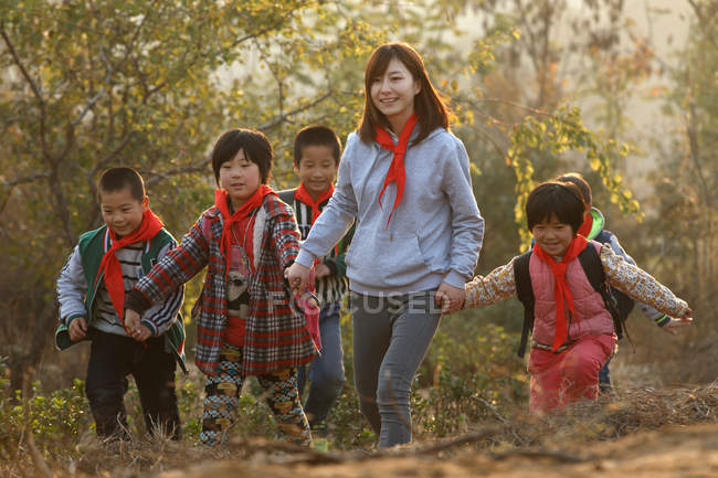 Outdoor activities for chinese rural female teacher and students — стокове фото