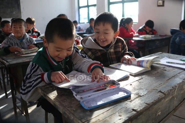 Studenti delle scuole cinesi che studiano con libri di testo nella scuola primaria rurale — Foto stock