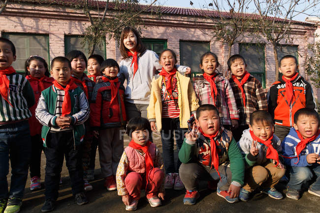 Сельская учительница и счастливые китайские ученики стоят перед школой и улыбаются перед камерой — стоковое фото