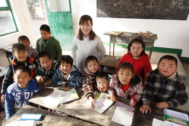 Vue en grand angle de l'enseignante rurale et des élèves chinois levant la main et souriant à la caméra en classe — Photo de stock