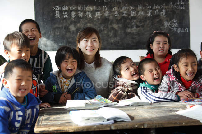Happy chinese rural female teacher and pupils in the classroom — Stock Photo