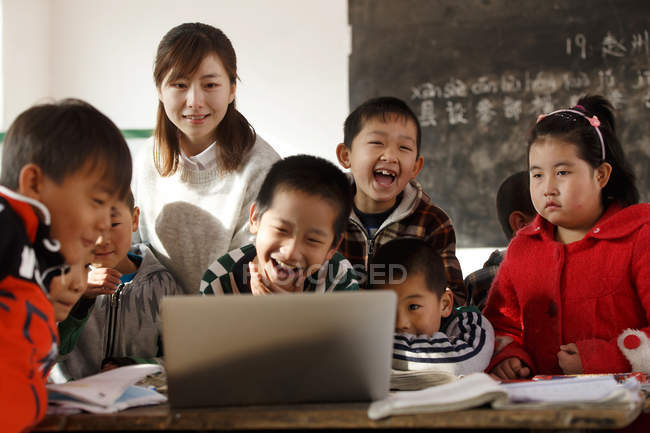 Rural female teacher and pupils using laptop together in classroom — стокове фото