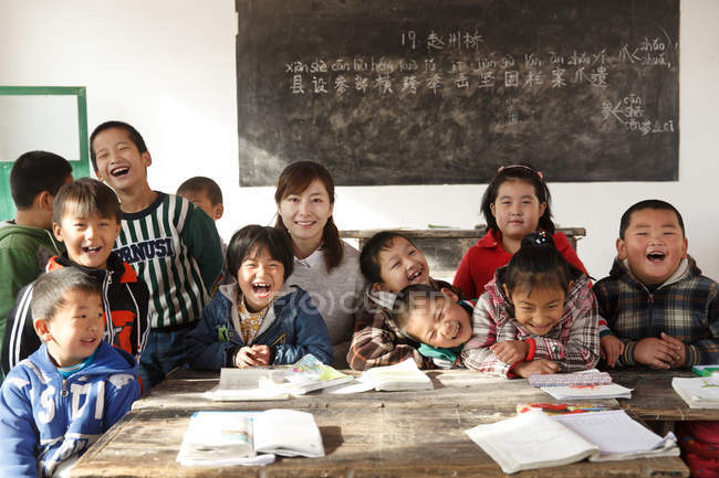 Chinese rural female teacher and pupils smiling at camera in the classroom — стокове фото