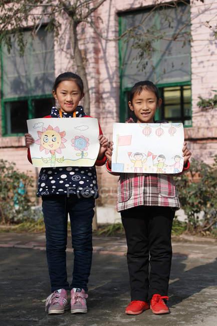 Ученики начальной школы с рисунками и улыбкой перед камерой во дворе школы — стоковое фото