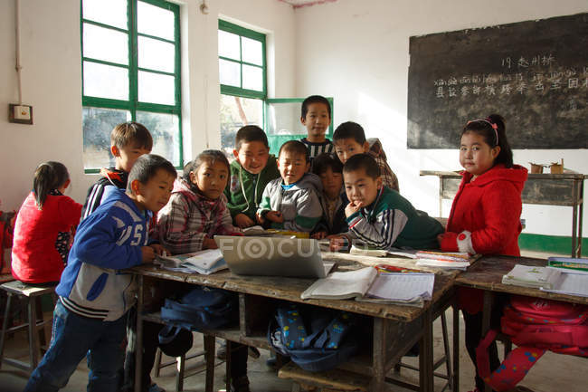 Chinese rural primary school students using laptop computer in classroom — Stock Photo