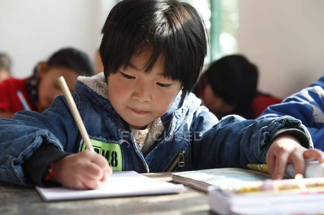 Chinese primary school students writing during class in rural school — Foto stock