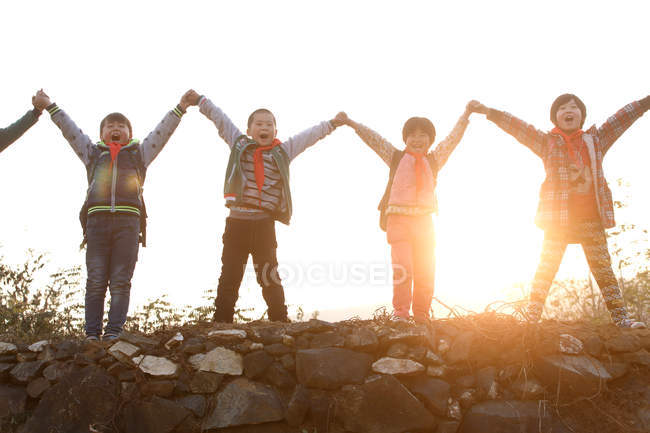 Happy rural pupils holding and raising hands while standing on hill at sunrise — Stock Photo