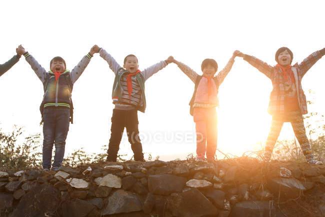 Allievi rurali felici che tengono e alzano le mani mentre sono in piedi sulla collina all'alba — Foto stock
