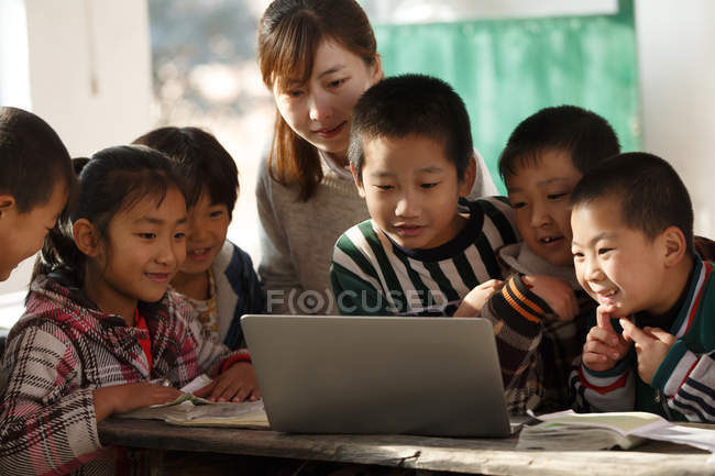 Rural female teacher and chinese pupils using laptop computer together in school — стокове фото