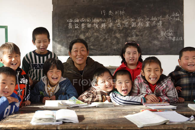 Rural female teacher and chinese pupils smiling at camera in the classroom — Stock Photo