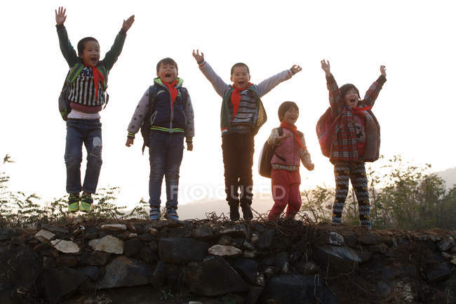 Happy rural chinese pupils raising arms and cheering outdoor — стокове фото