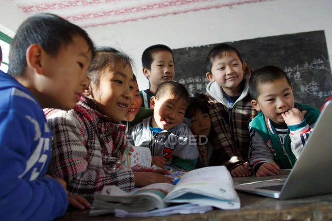 Chinese rural primary school students using laptop computer in classroom — стокове фото