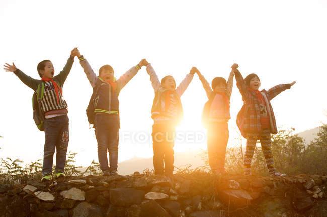 Щасливі сільські учні тримають і піднімають руки, стоячи на пагорбі на світанку — стокове фото