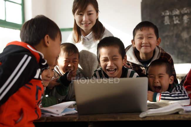 Сільська вчителька та учні з використанням ноутбука разом у класі — стокове фото